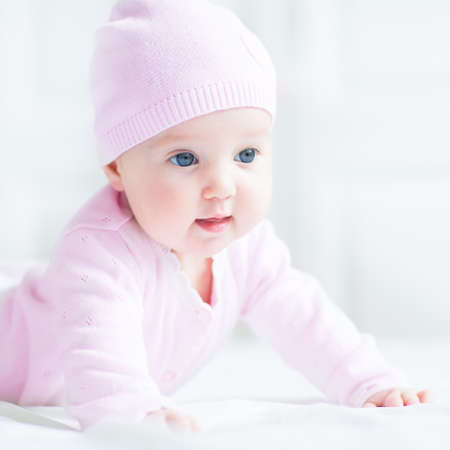 laughing baby: Happy smiling baby girl in a pink knitted hat Stock Photo