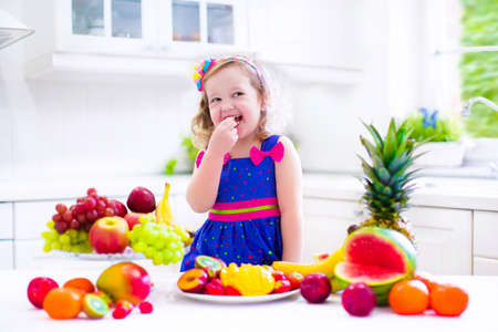Cute curly little girl in a colorful summer dress eating fresh tropical fruit and berry for healthy breakfast snack in a white sunny family kitchen photo