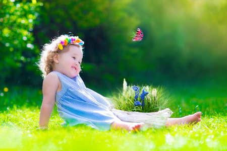 Niña linda del niño con el pelo rizado que llevaba un vestido azul de verano que se divierte viendo una mariposa y flores, relajarse en el jardín en un día soleado de primavera