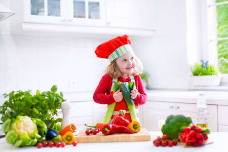 Happy little girl in a red chef hat and apron preparing healthy lunch with fresh raw vegetables, making salad with tomato, eggplant, pepper and cauliflower in a white kitchen at home photo