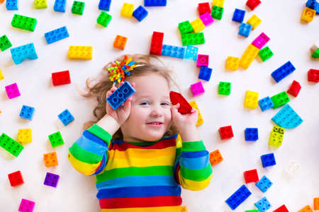 Cute funny preschooler little girl in a colorful shirt playing with construction toy blocks building a tower in a sunny kindergarten room photo