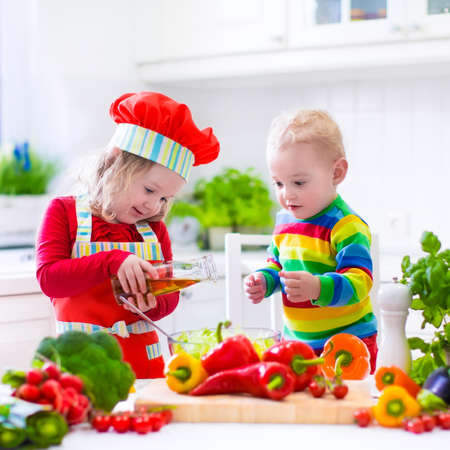 Two little children, adorable toddler girl in red chef hat and apron and funny baby boy preparing healthy lunch making delicious salad with fresh vegetables and garden herbs in a white sunny kitchen photo