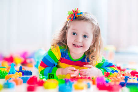 children playing with toys: Cute funny preschooler little girl in a colorful shirt playing with construction toy blocks building a tower in a sunny kindergarten room