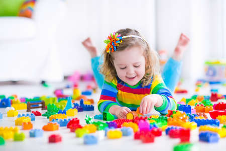 Cute funny preschooler little girl in a colorful shirt playing with construction toy blocks building a tower in a sunny kindergarten room