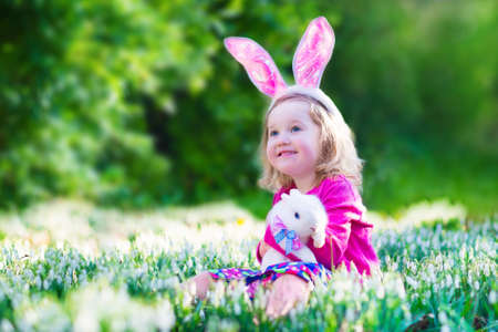 Adorable little girl, cute curly toddler in a colorful summer dress, playing with a real rabbit, having fun with her pet bunny in a beautiful garden with first spring snowdrop flowers Stock Photo - 37120600