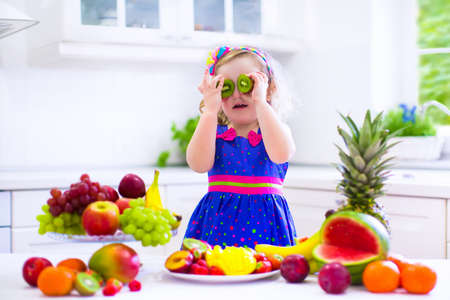 Cute curly little girl in a colorful summer dress eating fresh tropical fruit and berry for healthy breakfast snack in a white sunny family kitchen Stock Photo