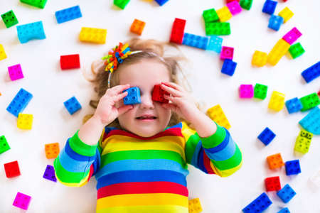 kid's day: Cute funny preschooler little girl in a colorful shirt playing with construction toy blocks building a tower in a sunny kindergarten room