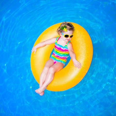 schwimmring: Nettes lustiges kleines Kleinkindmädchen in einem bunten Badesachen und Sonnenbrille entspannt auf einer aufblasbaren Spielzeug Ring schwebend in einem Pool, die Spaß während der Sommerferien in einem tropischen Resort
