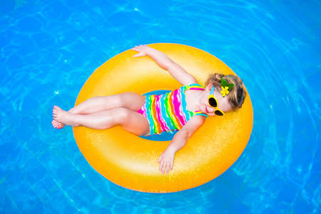 child swimsuit: Cute funny little toddler girl in a colorful swimming suit and sun glasses relaxing on an inflatable toy ring floating in a pool having fun during summer vacation in a tropical resort
