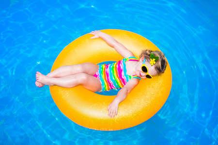 Nettes lustiges kleines Kleinkindmädchen in einem bunten Badesachen und Sonnenbrille entspannt auf einer aufblasbaren Spielzeug Ring schwebend in einem Pool, die Spaß während der Sommerferien in einem tropischen Resort Standard-Bild
