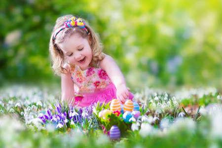 Schattig krullend peuter meisje in een roze zomer jurk spelen met Pasen eieren tijdens de eieren zoeken in een zonnige tuin met eerste witte lentebloemen Stockfoto