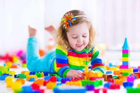 preescolar: Preescolar divertida linda de la niña en una camisa de colores jugando con bloques de juguete de la construcción la construcción de una torre en una sala de jardín de infantes soleado