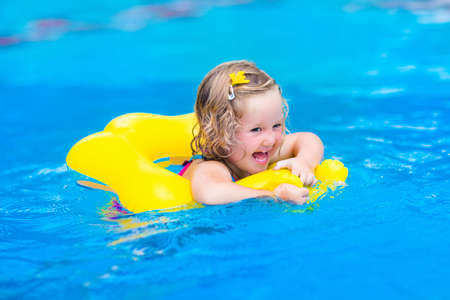 girl with rings: Cute funny little toddler girl in a colorful swimming suit and sun glasses relaxing on an inflatable toy ring floating in a pool having fun during summer vacation in a tropical resort