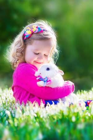 Niña adorable, niño rizado lindo en un vestido de verano de colores, jugando con un conejo de verdad, se divierte con su mascota conejo en un hermoso jardín con flores de campanillas primero de primavera Foto de archivo