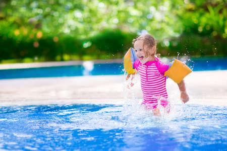 水と遊ぶカラフルな水着を身に着けている巻き毛の愛らしい少女が家族夏休み楽しんでトロピカル リゾートの美しいプールではね
