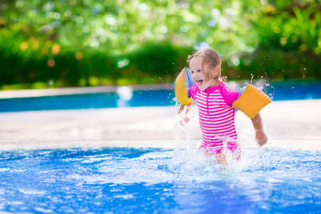 kids playing water: Adorable little girl with curly hair wearing a colorful swimming suit playing with water splashes at beautiful pool in a tropical resort having fun during family summer vacation Stock Photo
