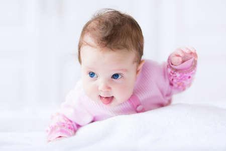 クロールする学習の楽しみを持っているピンクのカーディガンでかわいい赤ちゃんおかしい女の子