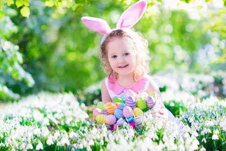 pascuas navide�as: Adorable ni�o ni�a rizado con orejas de conejo jugando con huevos de Pascua en una cesta blanca sentado en un jard�n soleado con primeras flores de primavera en blanco
