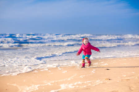 north holland: Funny little girl, cute happy toddler in a colorful jacket, running and jumping on the beach at the North Sea in Holland, Netherlands, having fun on a sunny winter day Stock Photo