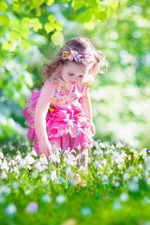 Adorable curly toddler girl in a pink summer dress playing with Easter eggs during egg hunt in a sunny garden with first white spring flowers