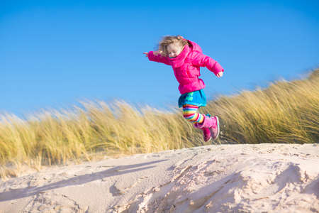 Happy funny little girl, adorable curly toddler, running and jumping in sand dunes enjoying family vacation at the North Sea, Holland, Netherlands on a sunny winter day at the beach Zdjęcie Seryjne