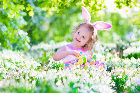Adorable curly toddler girl wearing bunny ears playing with Easter eggs in a white basket sitting in a sunny garden with first white spring flowers photo