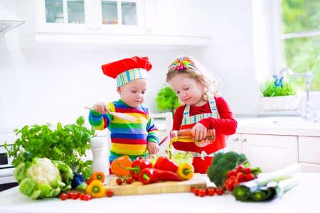 saludable: Dos peque�os ni�os, ni�o ni�a adorable en sombrero del cocinero rojo y delantal y beb� divertido que preparan el almuerzo saludable haciendo deliciosa ensalada con verduras frescas y hierbas del jard�n en una cocina blanca soleado Foto de archivo