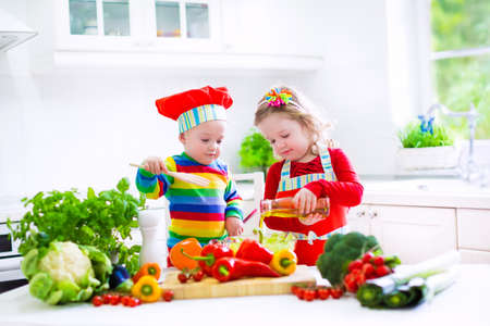 family eating: Two little children, adorable toddler girl in red chef hat and apron and funny baby boy preparing healthy lunch making delicious salad with fresh vegetables and garden herbs in a white sunny kitchen Stock Photo