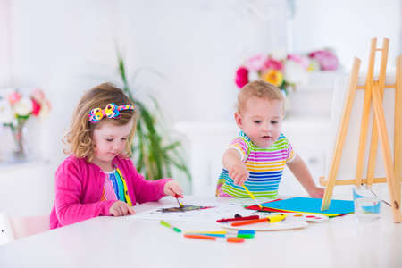 drawing room: Two happy preschool children, cute little girl and funny toddler boy, painting and drawing together with water color on canvas in a sunny class room with wooden easel, creative young artists at work