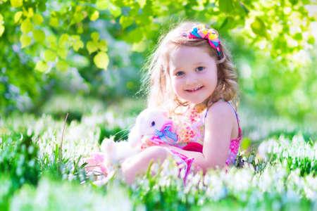 zanahoria: Ni�a adorable, ni�o rizado lindo en un vestido de verano de colores, jugando con un conejo de verdad, se divierte con su mascota conejo en un hermoso jard�n con flores de campanillas primero de primavera