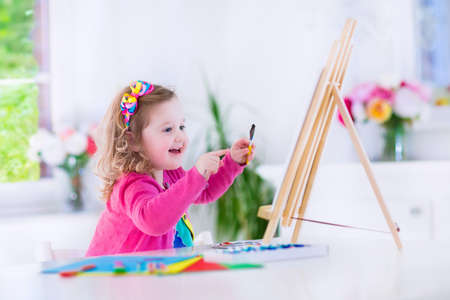 wood art: Cute happy little girl, adorable preschooler, painting with water color on canvas standing on a wooden easel in a sunny white room at home or elementary school, creative young artist at work Stock Photo