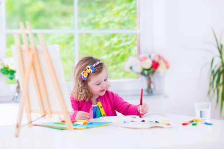 Linda niña feliz, adorable niño en edad preescolar, la pintura con el color del agua en la lona de pie sobre un caballete de madera en una habitación blanca soleado en casa o en la escuela primaria, joven artista creativo en el trabajo