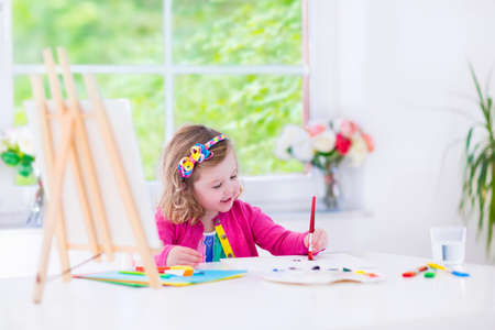 Cute happy little girl, adorable preschooler, painting with water color on canvas standing on a wooden easel in a sunny white room at home or elementary school, creative young artist at work Stockfoto