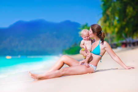 baby in suit: Young mother and her cute little baby running and playing on a beautiful tropical beach enjoying family summer holiday Stock Photo