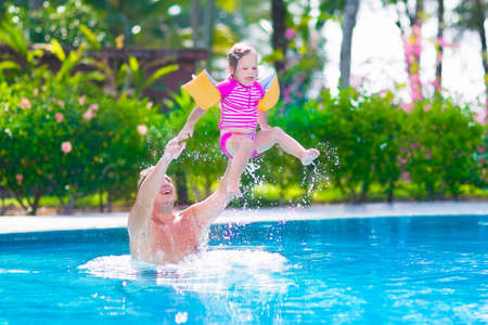 Happy active family, young father and his cute daughter, adorable toddler girl, playing in a swimming pool jumping into the water enjoying summer vacation in a beautiful tropical island resort