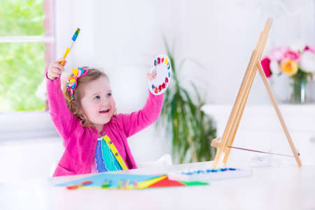Cute happy little girl, adorable preschooler, painting with water color on canvas standing on a wooden easel in a sunny white room at home or elementary school, creative young artist at work photo