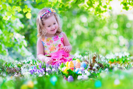 easter bunny: Adorable curly toddler girl in a pink summer dress playing with Easter eggs during egg hunt in a sunny garden with first white spring flowers
