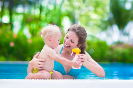 sun screen: Young mother and cute baby boy enjoying summer vacation in a tropical resort at a swimming pool, parent applying sun screen using lotion spray for safe tan and skin care