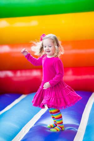 gente saltando: Niña preescolar divertido lindo en un vestido de colores de juego, saltando y saltando en un castillo inflable divirtiéndose en una fiesta de cumpleaños de los niños en un parque infantil en verano Foto de archivo