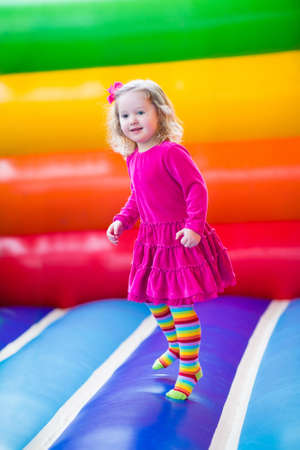 Cute funny preschool little girl in a colorful dress playing, jumping and bouncing in an inflatable castle having fun at a children birthday party on a kids playground in summer
