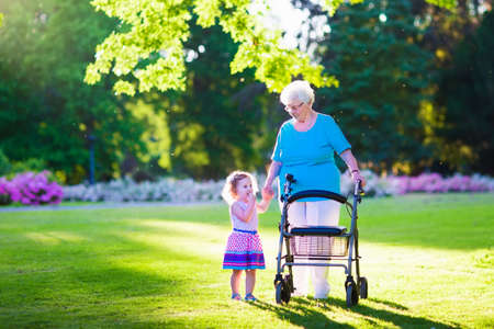 people with disabilities: Happy senior lady with a walker or wheel chair and a little toddler girl, grandmother and granddaughter, enjoying a walk in the park. Child supporting disabled grandparent.