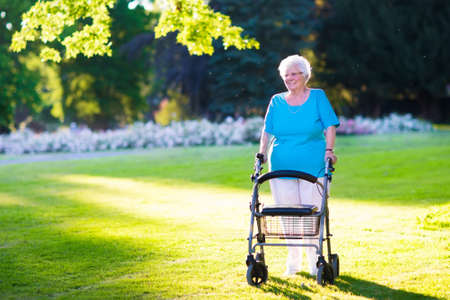 Happy senior handicapped lady with a walking disability enjoying a walk in a sunny park pushing her walker or wheel chair, aid and support during retirement concept.