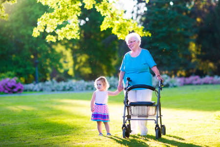 Happy senior lady with a walker or wheel chair and a little toddler girl, grandmother and granddaughter, enjoying a walk in the park. Child supporting disabled grandparent.