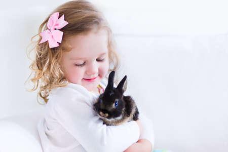 kinder: Feliz riendo niña jugando con un conejo bebé, abrazándola mascota conejito real y aprender a cuidar de un animal. Niño en un sofá blanco en su casa o jardín de infantes.