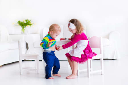 stethoscope boy: Two happy children, cute toddler girl and adorable baby boy, brother and sister, playing doctor and hospital using stethoscope toy and medical uniform, having fun at home or preschool
