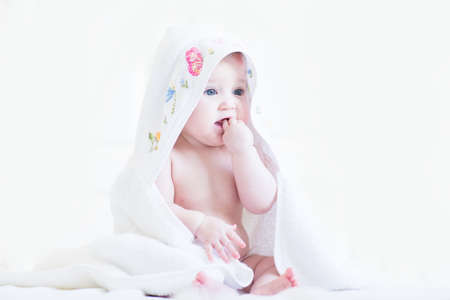 Sweet baby girl in a cross-stitched handmade towel photo