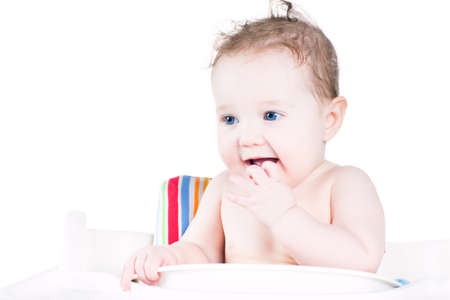 high chair: Adorable baby sitting in a high chair waiting for dinner Stock Photo