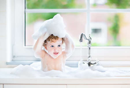 Funny little baby girl with wet curly hair taking a bath in a kitchen sink with lots of foam playing with water drops and splashes next to a big window with garden view 免版税图像