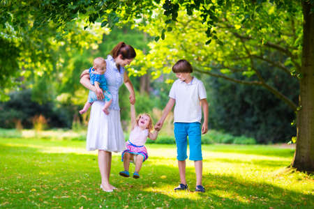 children walking: Happy family with three kids in a park. Young mother with children, little toddler girl, school age boy and baby playing in a sunny summer garden, walking and holding hands with her son and daughter.