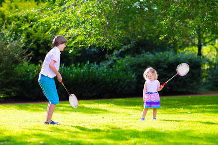 badminton: Active children playing badminton. Two happy kids, school age boy and little girl having fun on a family picnic in a park, enjoying sport games, running and jumping with tennis racket on a hot summer day outdoors.